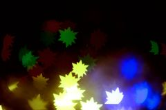 The Golden glare in the form a stars. A festive kaleidoscope, a bright light. Abstract composition of lights and figured bokeh. A good holiday background for royalty free stock photos