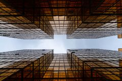 Golden glass building facade in worm eye view in linear view to see the clear sky / abstract architecture / architectural material royalty free stock photo