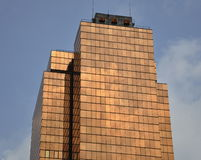 Golden glass building soaring into blue sky royalty free stock image