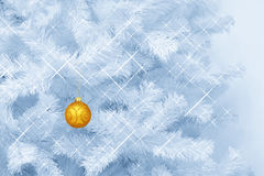 Golden glass glitter ornament Christmas bauble decoration hanging on a blue tinted Christmas tree Royalty Free Stock Photo