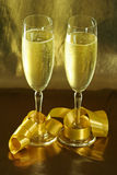 Golden glasses. 2 glasses of champagne with a golden background stock photos