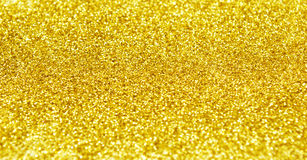 Golden glitter background. Yellow defocused glitter texture for wonderful holiday background Stock Image