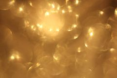 Golden glitter christmas abstract bokeh background. Blurred sparkles backdrop stock photo