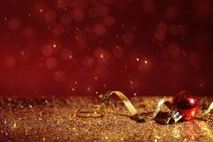 Golden glitter, Christmas ball and streamer against color background. stock images