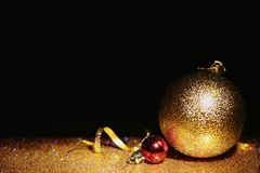 Golden glitter, Christmas balls and streamer against black background. Space for text royalty free stock images