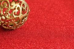 Christmas ornament motive. Golden glitter Christmas ornament motive, red glitter background, selective focus, free copy space royalty free stock image