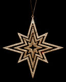 Golden glitter christmas star decoration on black Stock Image