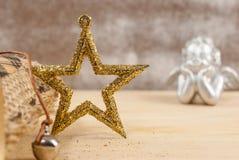 Golden glitter Christmas star over wooden background Stock Photo
