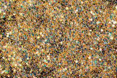 Glitter background. Golden glitter with colorful glassy pieces sprinkled over black background royalty free stock photography