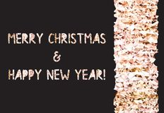 Golden glitter foil text on black background. Merry Christmas and Happy New Year lettering for invitation and greeting. Card, prints and posters Royalty Free Stock Photo