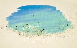 Golden glitter and glittering stars on abstract blue watercolor splash in vintage nostalgic colors. Golden glitter and glittering stars on abstract blue royalty free illustration