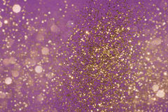 Golden Glitter Particles on Fabric. Golden glitter background on a purple fabric structure, fading into layered bokeh particles Stock Photography