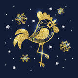 Golden glitter rooster and snowflakes on dark blue background. S Stock Photo