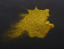 Golden glitter sand texture on black background. Golden glitter sand texture, handful spread on black, abstract background with copy space, top view. Yellow royalty free stock photos
