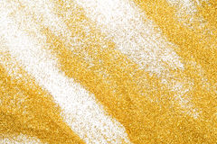 Golden glitter sand texture on white, abstract background. Yellow dusty shimmer decoration, shiny and sparkling. Holidays and glamour concept stock image