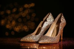 Golden glitter shoes on dark reflective surface against blurred background. Space for text stock image