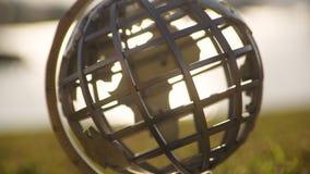A golden globe miniature. A close up steady shot of a golden globe spinning. The shot is taken during sunrise