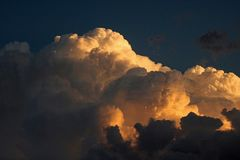 GOLDEN GLOW ON BILLOWING CUMULUS CLOUD. Billowing cumulus cloud with golden glow in the late afternoon at sunset Stock Photos
