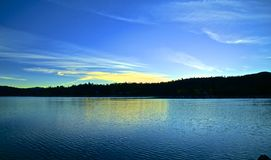 Sunrise Lake Arrowhead. Golden glow of sunrise reflects in blue calm waters of Lake Arrowhead California at dawn Royalty Free Stock Photography
