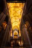 Golden glowing ceiling beams extend through church Stock Images