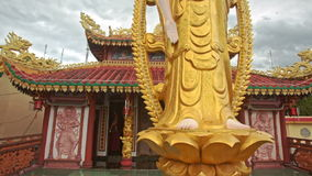 Golden God Statue against Pagoda in Buddhist Temple stock video