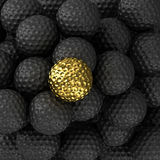 Golden golf ball with black ball Stock Photography
