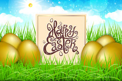 Golden gpld eggs in a field of grass with blue sky. happy easter lettering modern calligraphy, vector Royalty Free Stock Photos