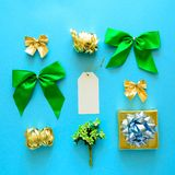 Golden and green Christmas gift boxes and decorations on blue background. Flat lay. Top view.  royalty free stock photos
