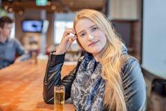 Golden-haariges blondes Mädchen, das in einer Bar ein alkoholisches Getränk trinkend sitzt stockfoto