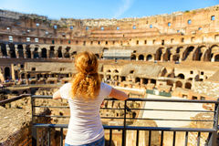 The golden-haired female tourist looks at the Colosseum, Rome Stock Photo