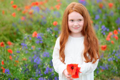Golden-haired girl standing among flowering meadows and smiles s Stock Image