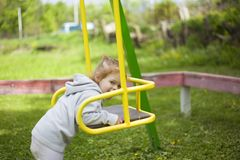 Golden-haired little girl gathered to climb out on the swing royalty free stock photos