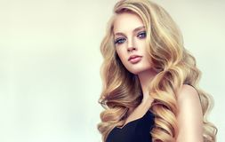 Golden haired woman with voluminous, shiny and curly hairstyle. Frizzy hair. Young golden haired woman with voluminous, shiny and wavy hair. Beautiful model royalty free stock photo