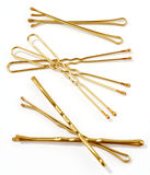 Hairpins. Golden hairpins over white background Stock Photo