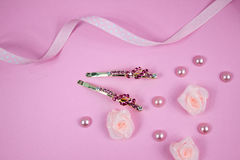 Golden hairpins with pink gemstone and pink polka dot ribbon on pink background. Golden hairpins with pink gemstone, pink polka dot ribbon, pearls and roses on Royalty Free Stock Image