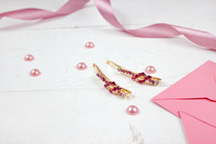 Golden hairpins with pink gemstone and pink ribbon on pink background. Golden hairpins with pink gemstone, pearls, envelope and pink ribbon on pink background royalty free stock photo