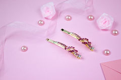 Golden hairpins with pink gemstone and pink ribbon on pink background. Golden hairpins with pink gemstone, pearls, envelope and pink ribbon on pink background Royalty Free Stock Image