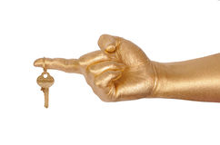 Golden hand with a gold key Stock Photography