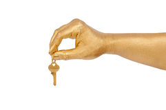 Golden hand with a key over white Royalty Free Stock Photography