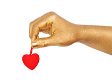 Golden hand with a red heart Royalty Free Stock Image