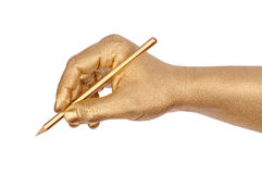 Golden hand writes by a pencil Royalty Free Stock Photo