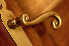 Golden handle and door. Gold handle and wooden door close up symbol of quality real estate or home Stock Images