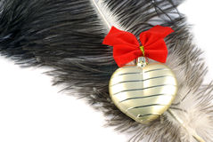 Golden heart. With red bow on ostrich feather Royalty Free Stock Photo