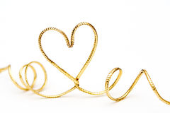 Golden heart. Golden ribbon bended to heart shape, isolated on white Stock Photography