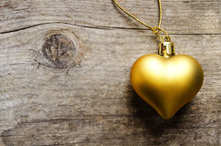 Golden heart. Over an aged wooden background Royalty Free Stock Images