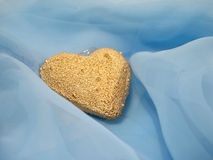 Golden heart on a blue background royalty free stock image