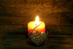 Golden heart and burning candle Royalty Free Stock Image
