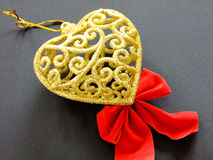 Golden Heart. Christmas Decoration golden Heart on black Background with red Ribbon under Royalty Free Stock Photo