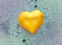 Golden heart on cracked background Stock Photos