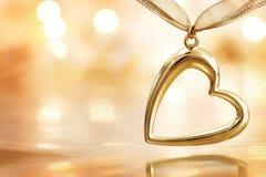 Golden heart on defocused lights background stock images